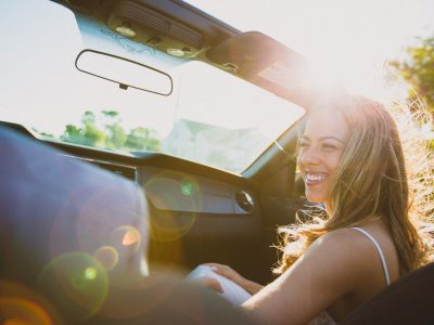 smiling woman sitting inside the vehicle at daytime
